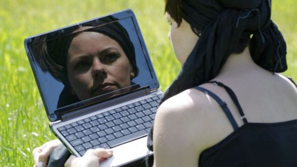 A woman looking at her reflection in a computer screen
