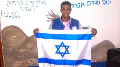 Ethiopian Jew Sintayehu Shifaraw holding up an Israeli flag
