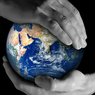 Picture of two hands holding a globe of the Earth